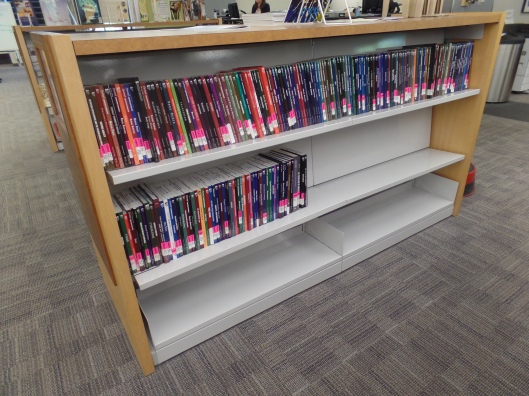 Library Shelves with books with pink debate books on them