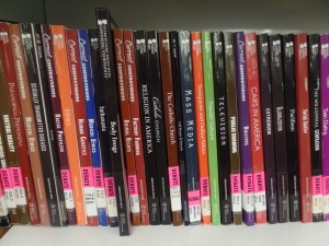 Close-up of a part of a shelf of debate books with pink labels