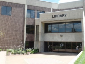 Brick and Cement building with entrance doors and sign that says Library